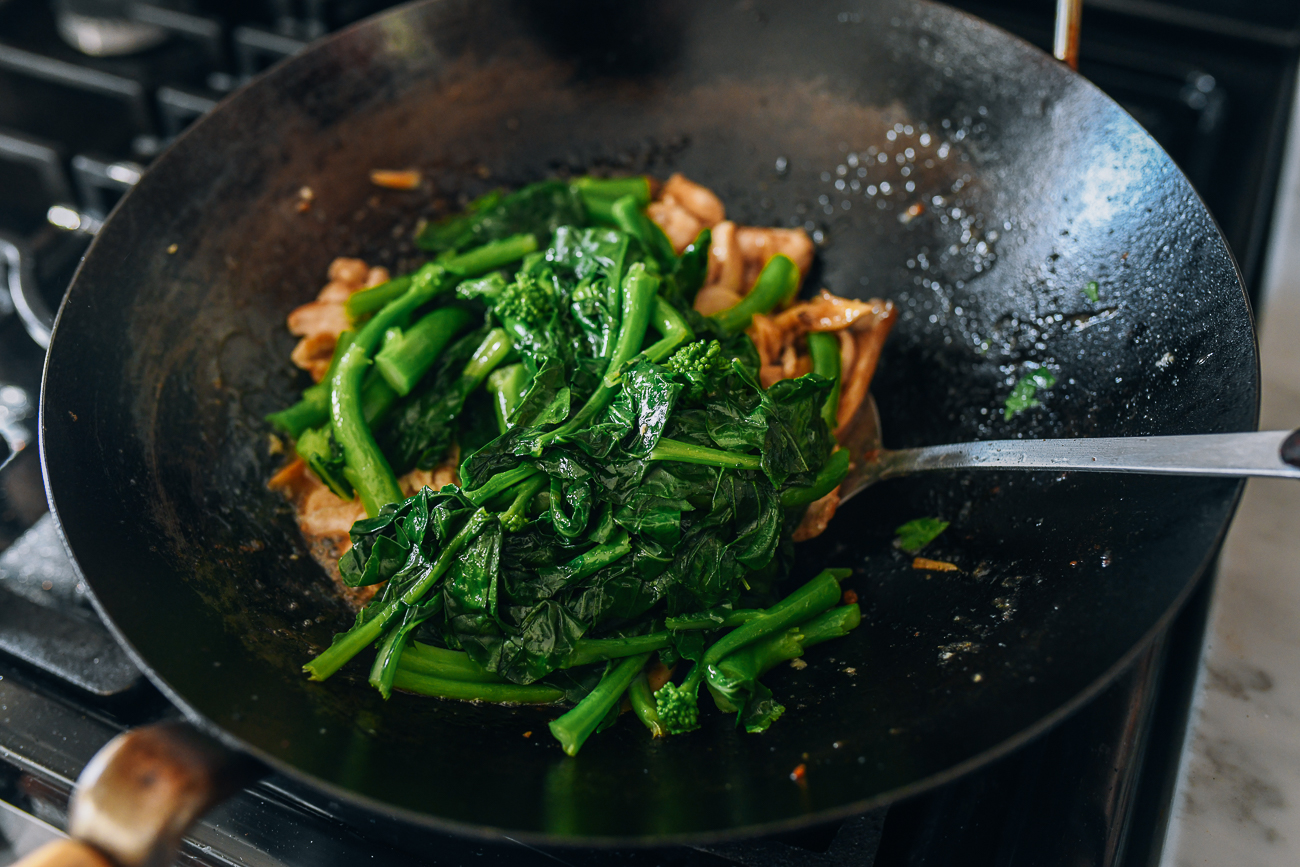 Adding blanched Chinese broccoli to other ingredients in wok