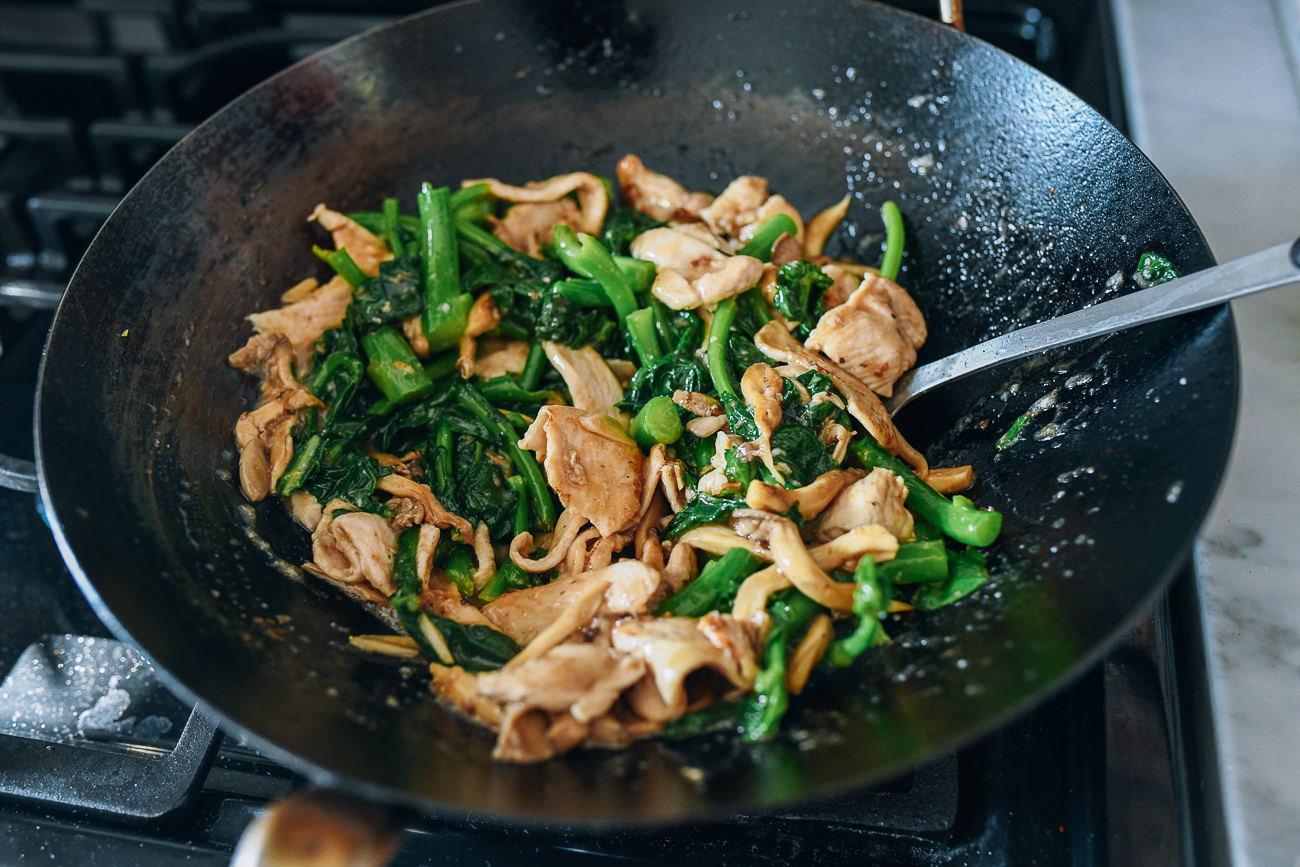Stir-frying chicken, chinese broccoli, and mushrooms