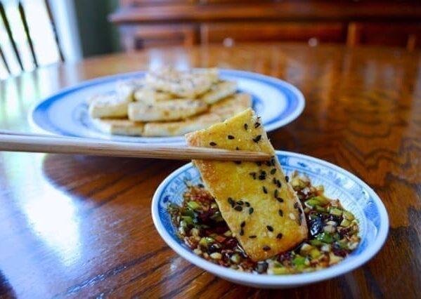 Dipping Pan-fried Tofu in Sauce