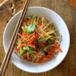 Bowl of noodles with julienned vegetables and chopsticks