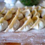 Folded Chinese dumplings on floured board