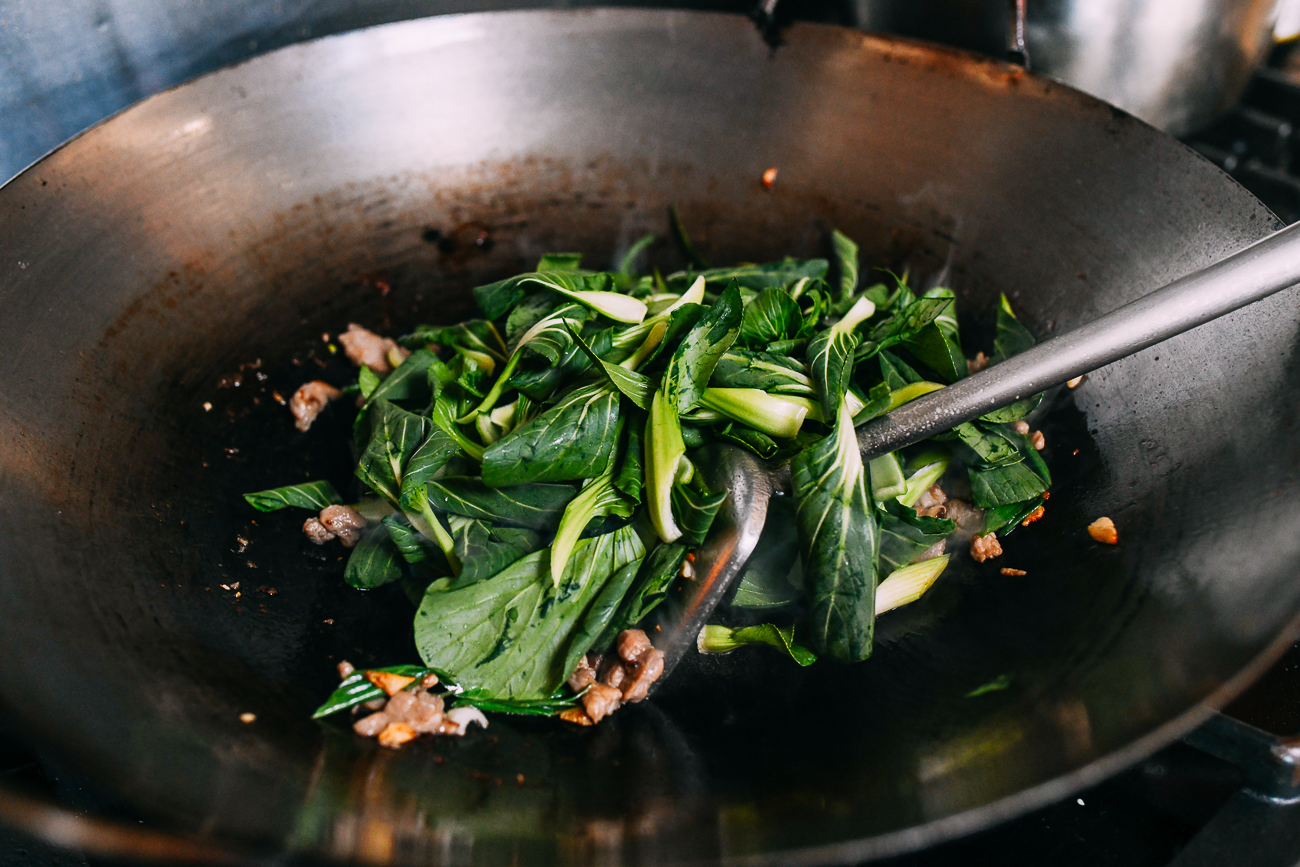 Adding bok choy to wok