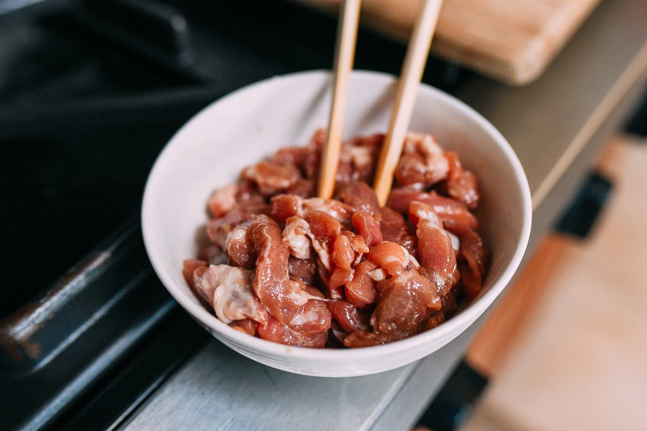 Marinated julienned pork in bowl with chopsticks