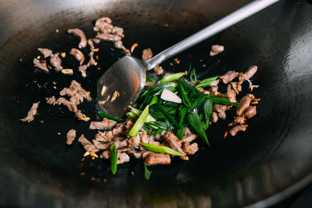 Adding scallions to pork in wok