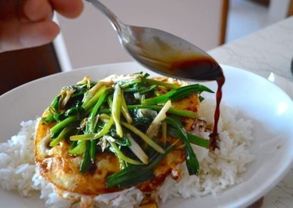 Spooning soy sauce over fried egg with scallions over rice