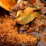 Adding coconut flakes to Indian lamb curry