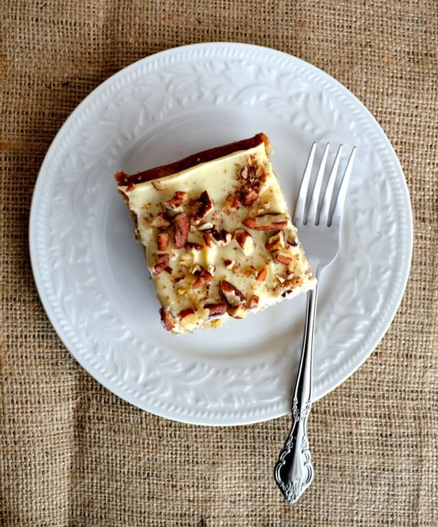 square slice of cake with cream cheese frosting and chopped pecans