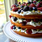 Three layer cake with whipped cream and fresh berries