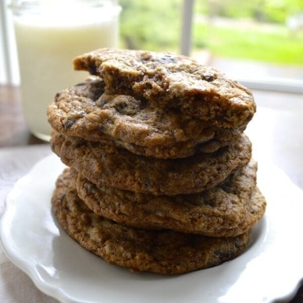 Pile of chocolate chip nut cookies with glass of milk