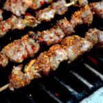 Beijing lamb skewers on grill with chili flakes