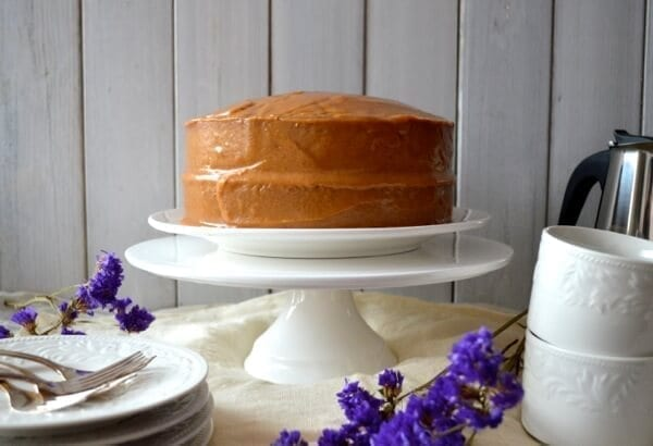 Peanut butter cake on cake stand with purple flowers