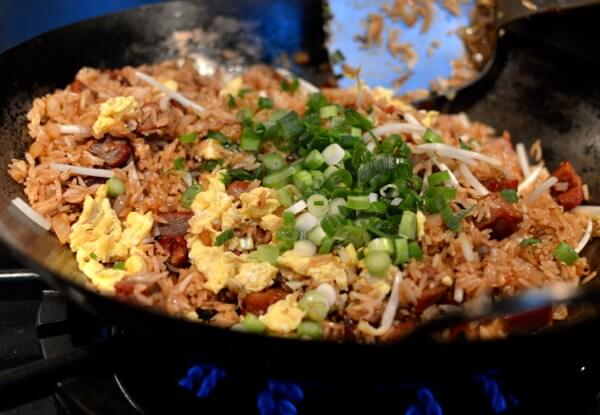 Adding scallions to fried rice, by thewoksoflife.com