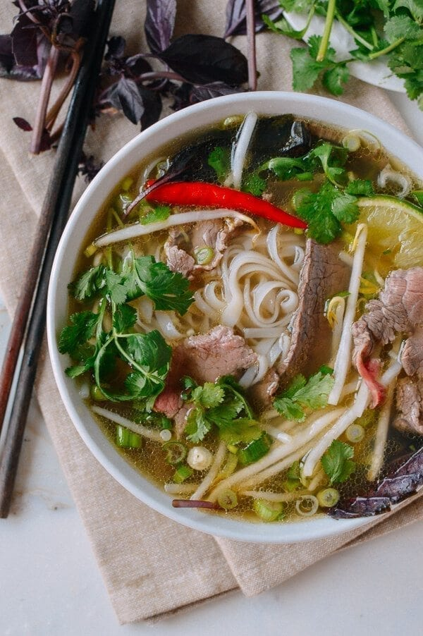 Bowl of pho with beef and herbs, by thewoksoflife.com