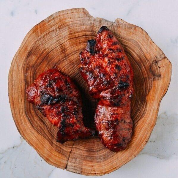 Grilled char siu on wood cutting board