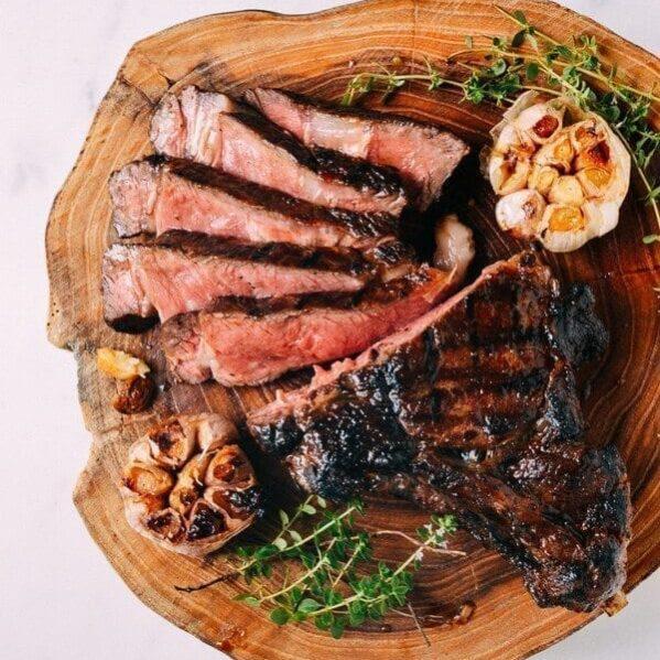 Sliced ribeye steak with roasted garlic on cutting board