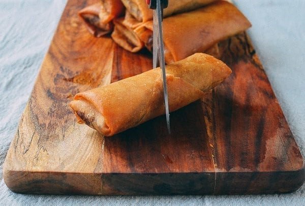 Cutting spring roll in half with scissors, thewoksoflife.com