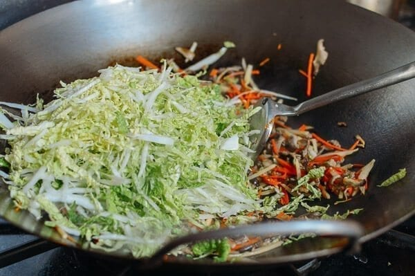 Adding shredded napa cabbage, by thewoksoflife.com