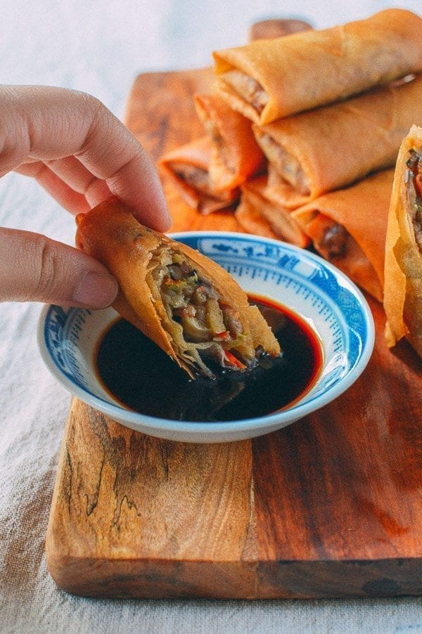 Dipping spring roll in sauce, thewoksoflife.com