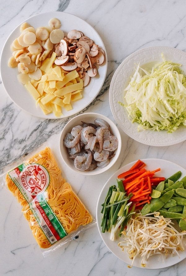 Take the shrimp and noodles out of the refrigerator, and let them come up to room temperature. One trick for the noodles is to soak the whole bag (unopened) in hot water, which speeds up the warming process without making the noodles soggy. If you can't find lo mein noodles, you can actually substitute dried linguini. Just cook until al dente, drain, and immediately toss with 1 tablespoon of vegetable oil, working the oil into the pasta so the noodles don't stick together. Always prepare your noodles just before you are ready to make the dish, so they don't dry out and remain at room temperature or warmer. This makes the stir-frying process much easier. Combine the sugar, soy sauces, oyster sauce, sesame oil, and white pepper in a bowl until the sugar is dissolved and set aside. Heat a large wok over high heat until it just starts to smoke, and add 1 tablespoon of oil around the perimeter of the wok. Quickly spread the shrimp around your wok and let them sear for 10-15 seconds on each side. Immediately transfer the shrimp to a plate and set aside. Return the wok to the highest heat possible and add 2 tablespoons oil, along with the garlic. After a few seconds, add the mushrooms, carrots, bamboo shoots, and water chestnuts and stir-fry for 30 seconds. Next, spread the Shaoxing wine around the perimeter of the wok, and then add the napa cabbage. Stir-fry for another 30 seconds. Spread the noodles evenly over the vegetables and give everything a good stir for 1 minute. Now, you can see why you want everything at room temperature, or everything will be overcooked and mushy by the time it heats up! At this point, the noodles should be softened, so add in the sauce mixture you set aside earlier and mix until everything is well combined. Stir-fry for another 30 seconds using a scooping motion, until the sauce is well distributed. Add in the shrimp, snow peas, bean sprouts, and scallions. Mix well for another 2 minutes and serve!