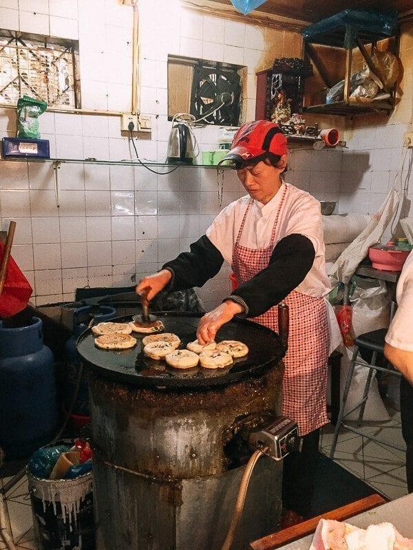 woman frying Shanghai Scallion Pancakes by thewoksoflife.com