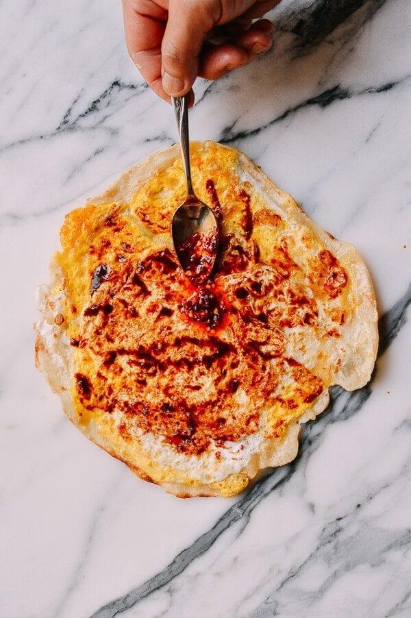 spreading sauce on Jidan Bing: The Chinese Breakfast of Champions, by thewoksoflife.com