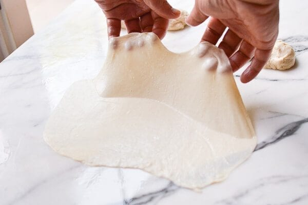 lifting thin oiled dough, by thewoksoflife.com