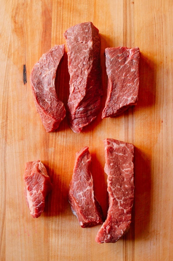 beef chuck steak pieces on a cutting board by thewoksoflife.com