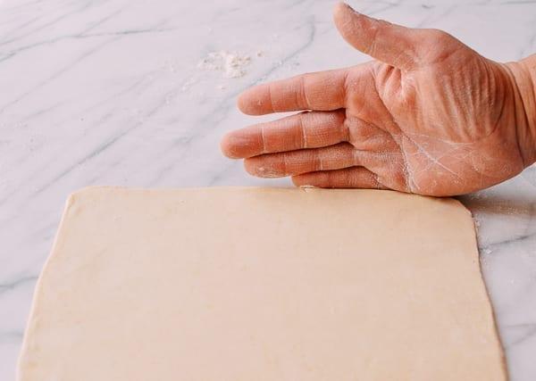 Using hands to straighten pastry edges, thewoksoflife.com