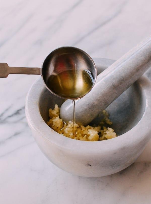 Mixing crushed garlic with olive oil, thewoksoflife.com