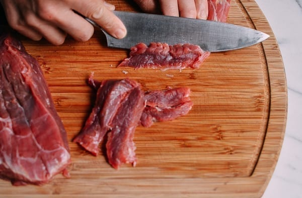 slicing beef flank steak on a cutting board by thewoksoflife.com