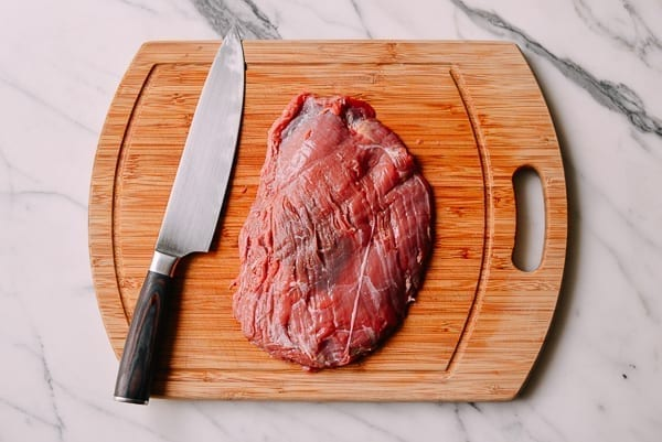 beef flank steak on a cutting board by thewoksoflife.com