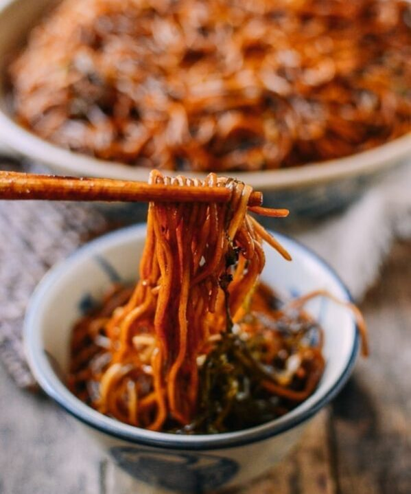 Picking up scallion oil noodles with chopsticks, thewoksoflife.com