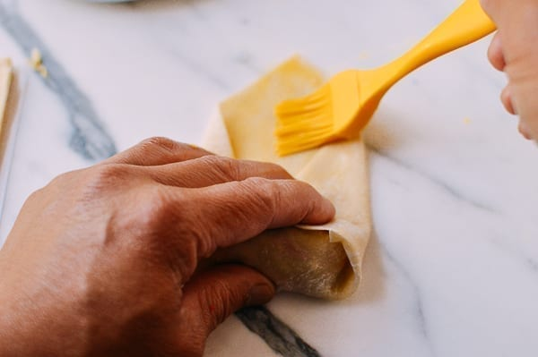 Brushing egg roll wrapper with egg wash to seal, thewoksoflife.com