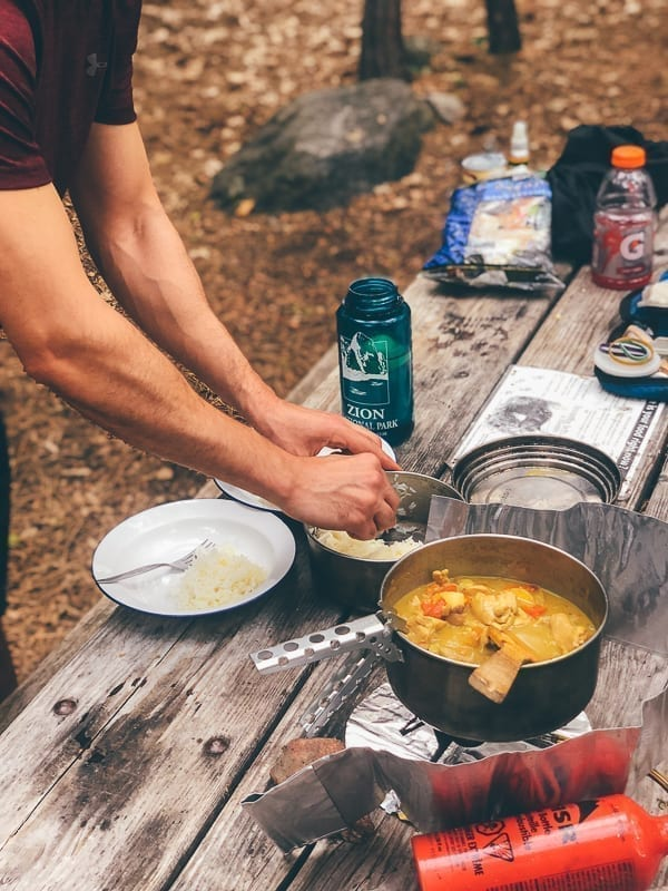 Cooking chicken curry over camping stove, thewoksoflife.com