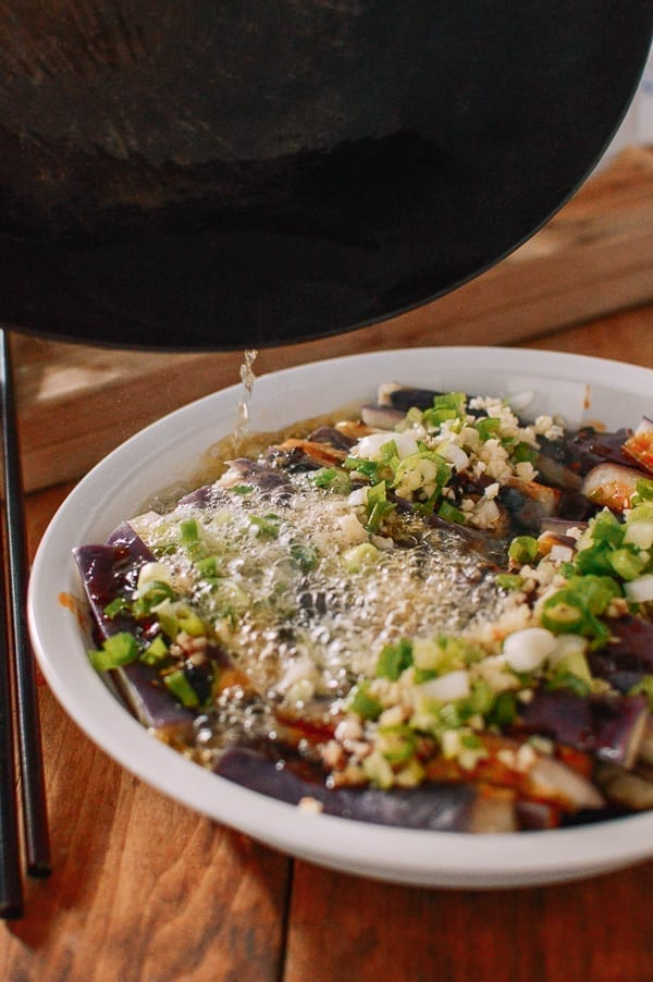 Pouring hot oil over steamed eggplant with garlic and scallions, thewoksoflife.com