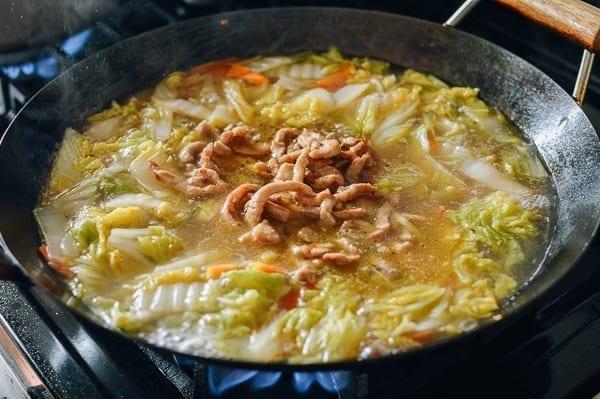 Stirring the pork into the soup, thewoksoflife.com