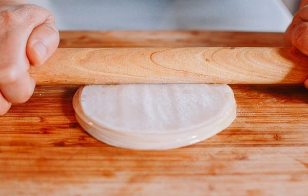 Pressing stack of dumpling wrappers with rolling pin, thewoksoflife.com