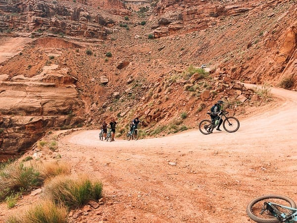 Mountain bikers walking on Schafer trail on White Rim trail Moab Utah by thewoksoflife.com