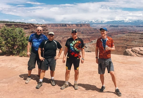 Mountain bikers group photo at top of Schafer trail on White Rim trail Moab Utah by thewoksoflife.com
