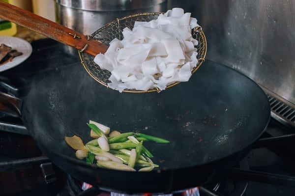 Adding rice noodles to wok, thewoksoflife.com