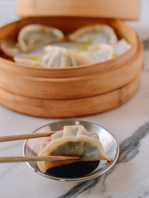 Dipping dumpling in sauce, thewoksoflife.com