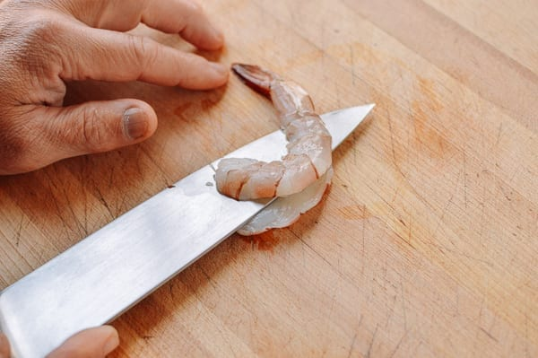Slicing lengthwise through a peeled shrimp