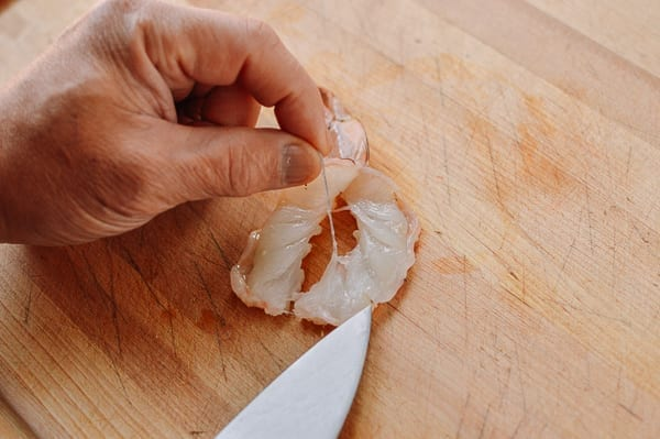 Removing vein from a shrimp that has been sliced in half lengthwise