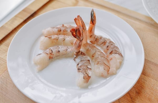 Three halved shrimp arranged on a plate with tails sticking up