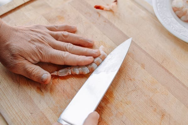 Slicing into the back of a peeled shrimp with chef's knife