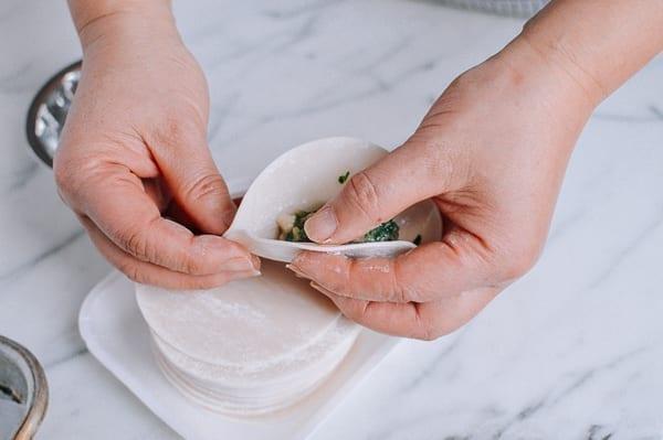 Pinching dumpling wrapper together at bottom corner, thewoksoflife.com