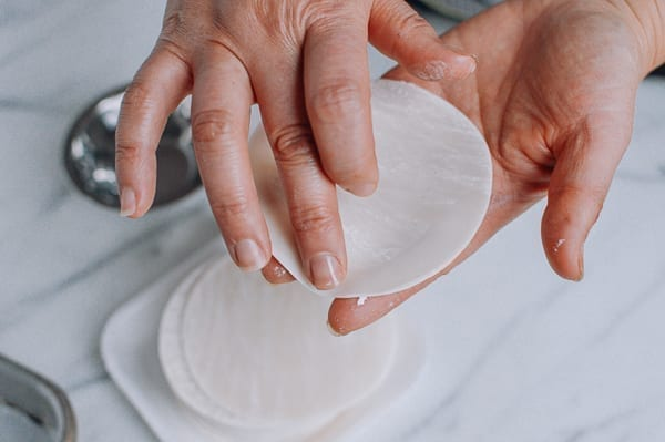 Using a finger to moisten outer edges of dumpling wrapper, thewoksoflife.com