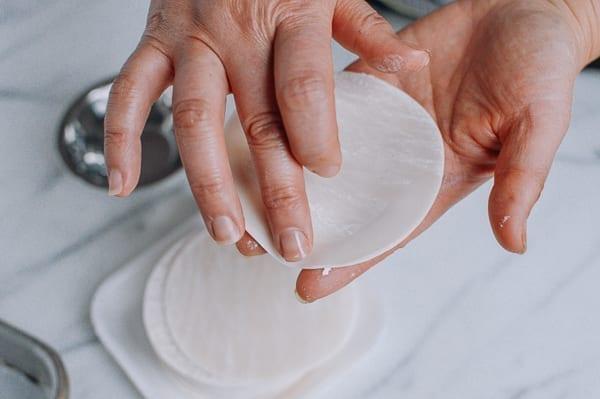 Using a finger to moisten outer edges of dumpling wrapper, thewoksoflife.com