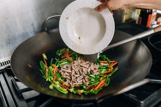 Adding the pre-cooked pork back to stir-fry in wok