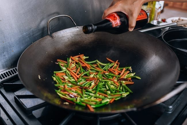 Adding Shaoxing wine to the wok
